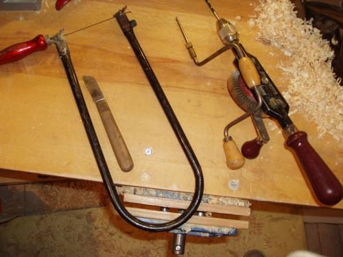 Unelte pentru realizarea unui elicopter: fierăstrău traforaj, cuțit și mașină de găurit